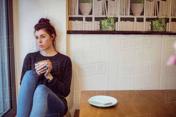 Hipster drinking a cup of coffee sitting on the floor Royalty-free stock photo