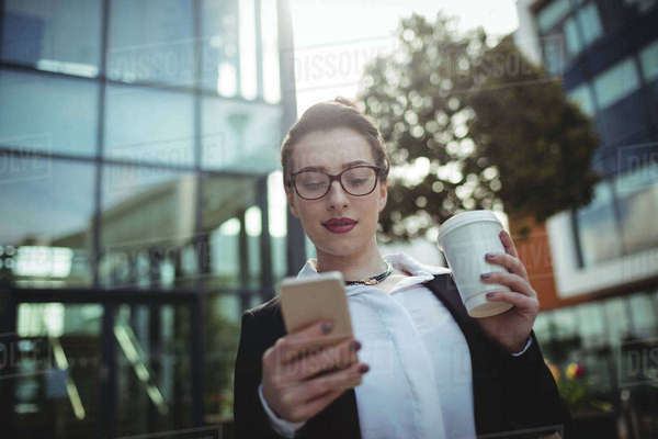 Businesswoman using mobile phone outside office building Royalty-free stock photo