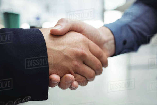 Business people shaking hands in airport terminal Royalty-free stock photo