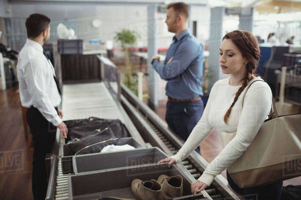 Woman putting shoes into tray for security check at airport Royalty-free stock photo