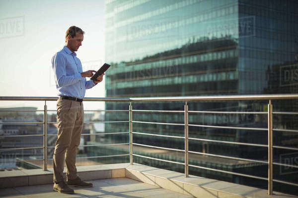 Businessman using digital tablet while standing in balcony at office Royalty-free stock photo