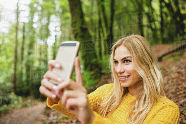 Beautiful blonde woman taking picture in the woods Royalty-free stock photo