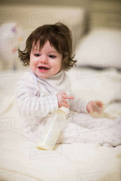 Cute baby playing with the bottle on the bed at home Royalty-free stock photo