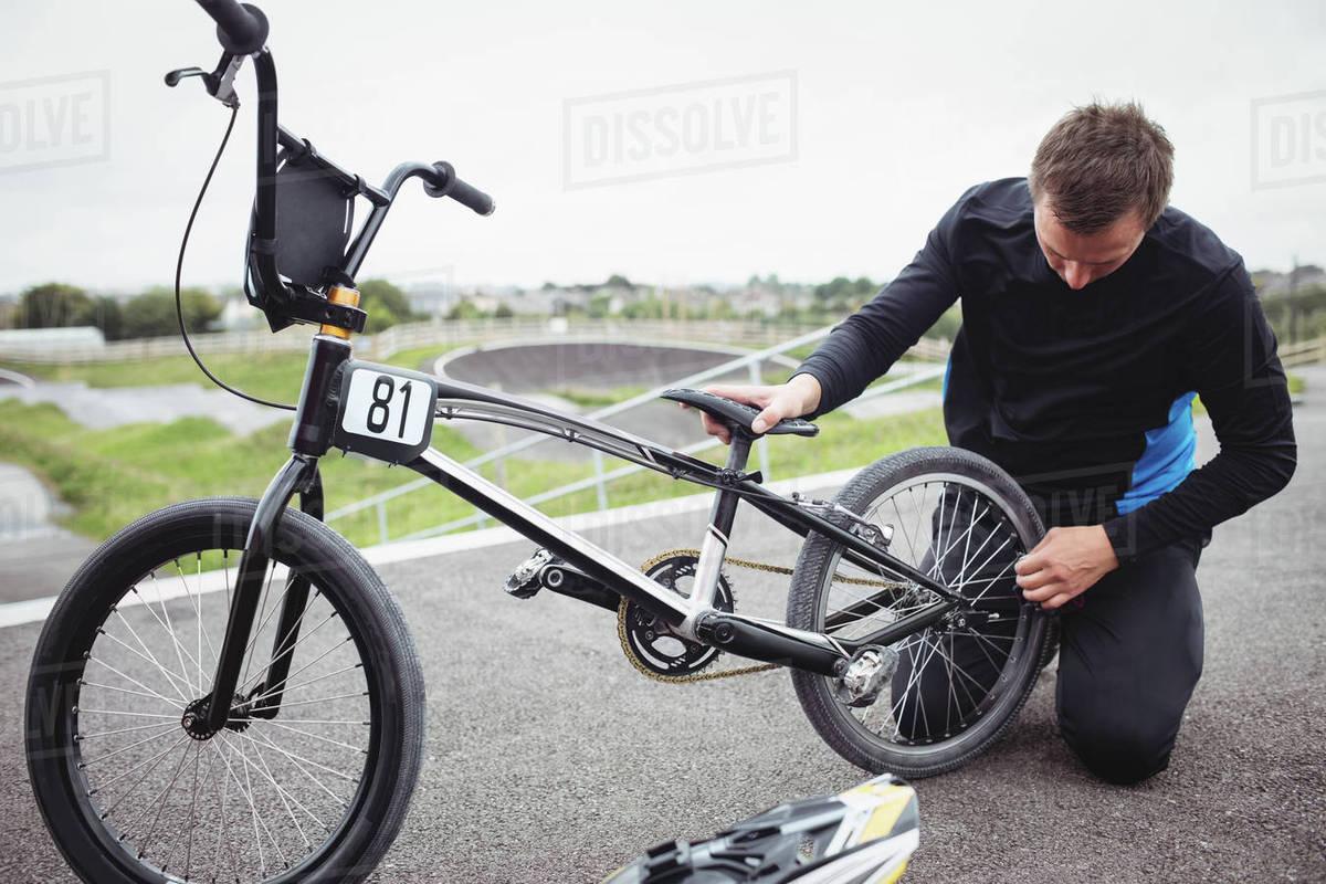 cyclist repairing a bmx bike in skatepark stock photo dissolve