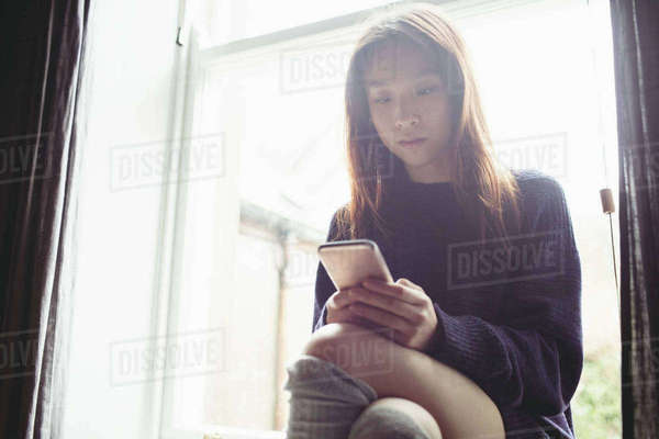 Brunette sitting on the window using her smartphone at home Royalty-free stock photo