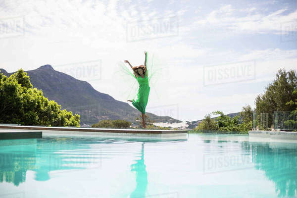 Elegant woman dancing by the pool on a summers day Royalty-free stock photo