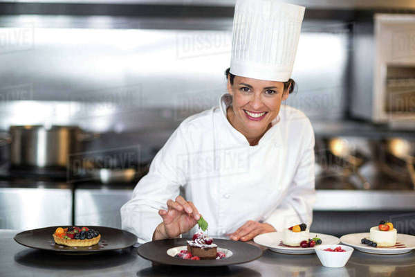 Chef putting finishing touch on dessert in a commercial kitchen Royalty-free stock photo