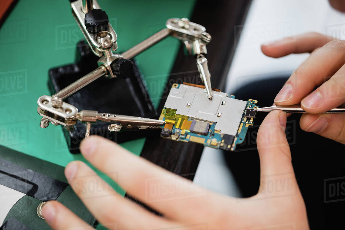 Man Repairing Mobile Phone In A Service Centre Stock Photo Dissolve Repair Of Circuit Board Used Pc Computer Royalty Free Clip