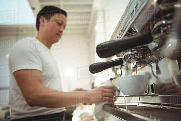 Side view of male barista making espresso in coffee shop Royalty-free stock photo