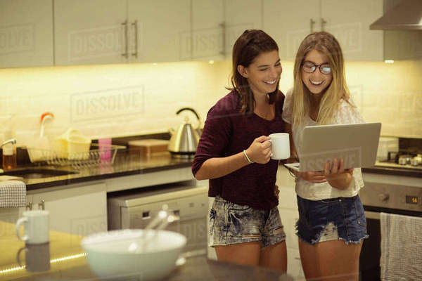 Happy friends using laptop while having coffee at home Royalty-free stock photo
