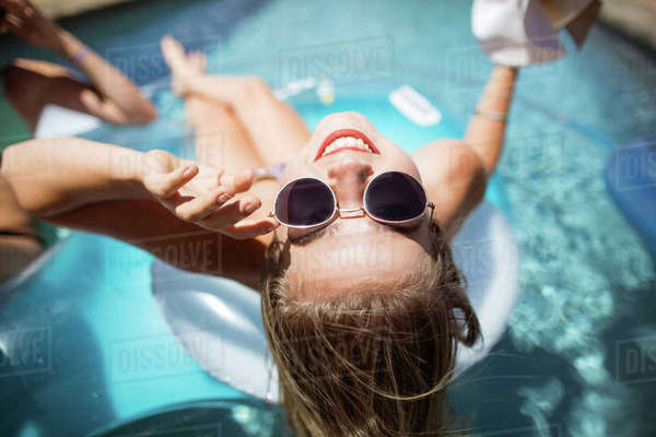 Beautiful woman relaxing in swimming pool on a sunny day Royalty-free stock photo