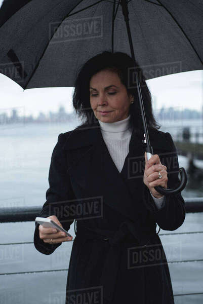 Woman using phone while holding umbrella by river during rainy season Royalty-free stock photo