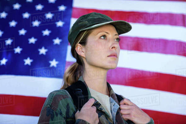 Soldier standing in front of american flag on a sunny day Royalty-free stock photo