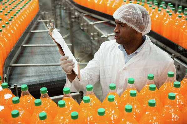 High angle view of male worker reading clipboard while inspecting bottles in juice factory Royalty-free stock photo
