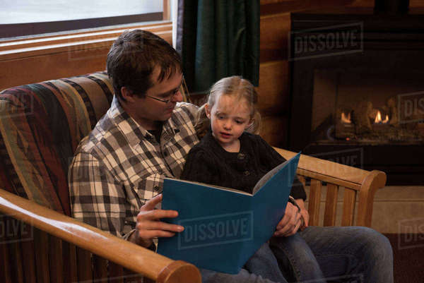 Father reading story book to daughter on chair at home Royalty-free stock photo