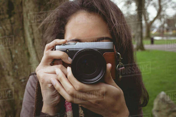 Close-up of woman taking photo from digital camera in park Royalty-free stock photo