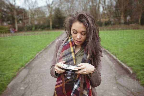 Woman holding digital camera in park Royalty-free stock photo