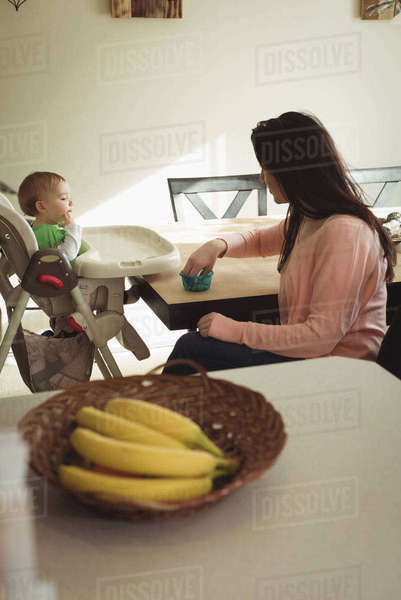 Mother interacting with her baby girl while feeding food at home Royalty-free stock photo