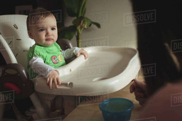Baby looking at her mother while sitting in high chair at home Royalty-free stock photo