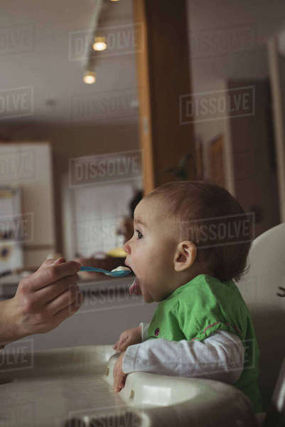 Mother feeding her baby in kitchen at home Royalty-free stock photo
