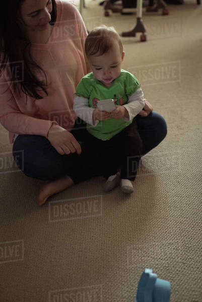 Baby girl sitting on her mothers lap using mobile phone in living room Royalty-free stock photo