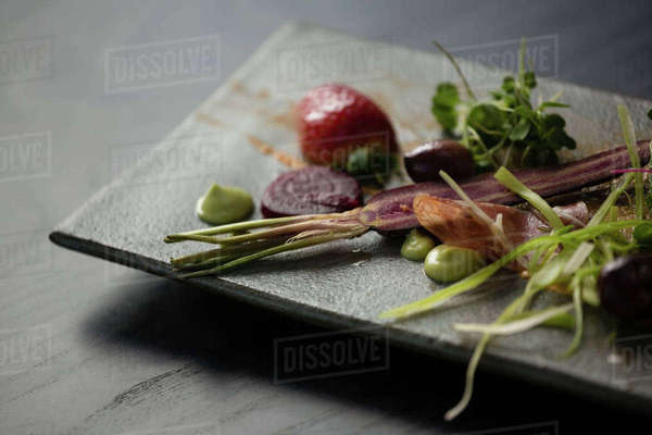 Close up of salad on stone tray at table in cafe Royalty-free stock photo