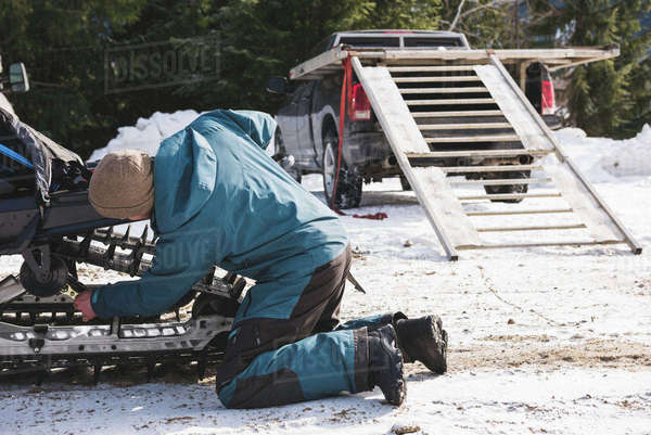 Man repairing snowmobile on a sunny day during winter season Royalty-free stock photo