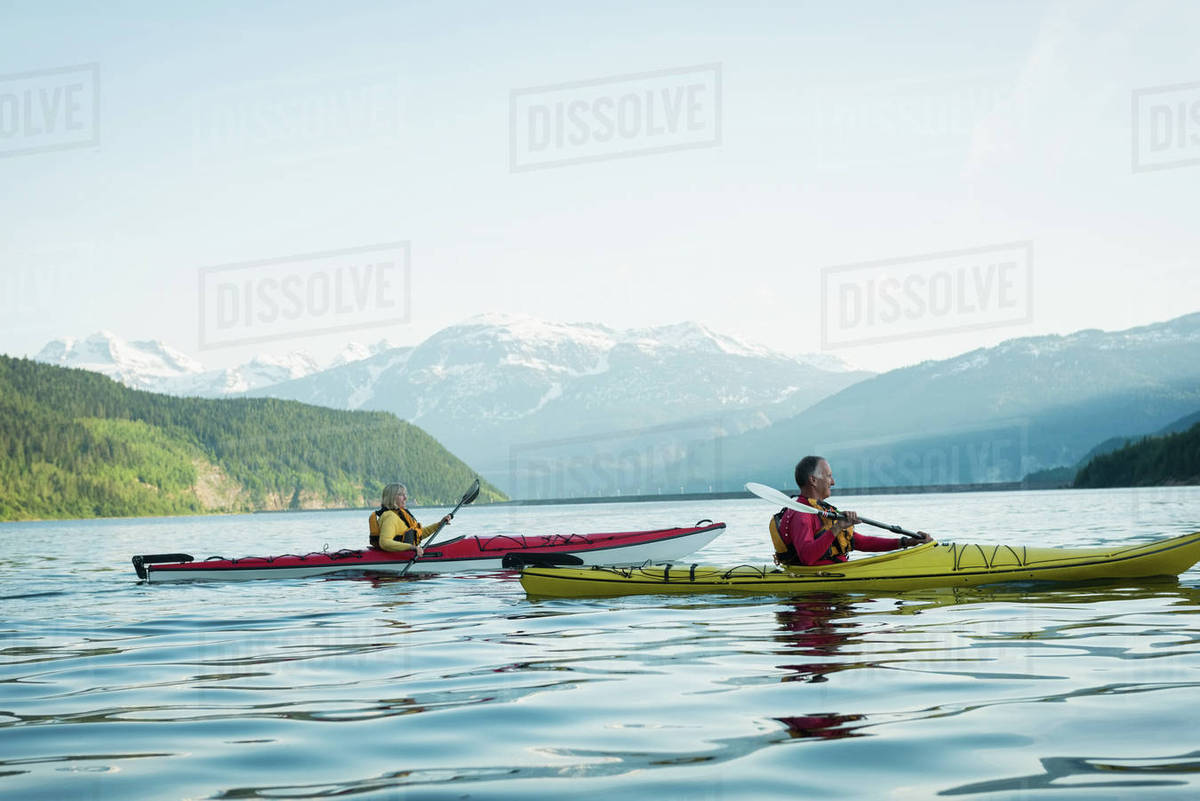 Side View Of Couple Kayaking By Mountains Against Sky