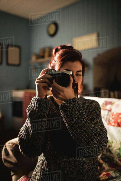 Young woman taking a picture with her camera at home Royalty-free stock photo