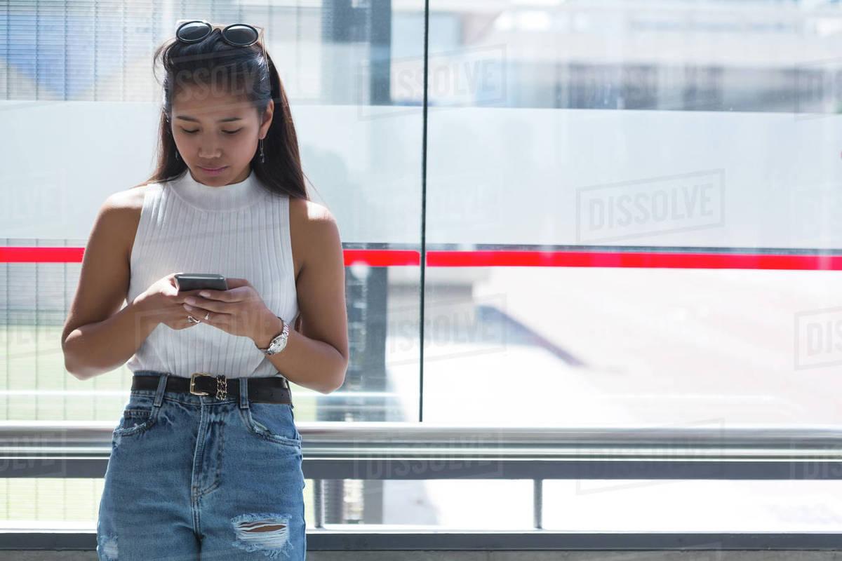 Teenage Girl Using Mobile Phone At Bus Stop - Stock Photo -6368