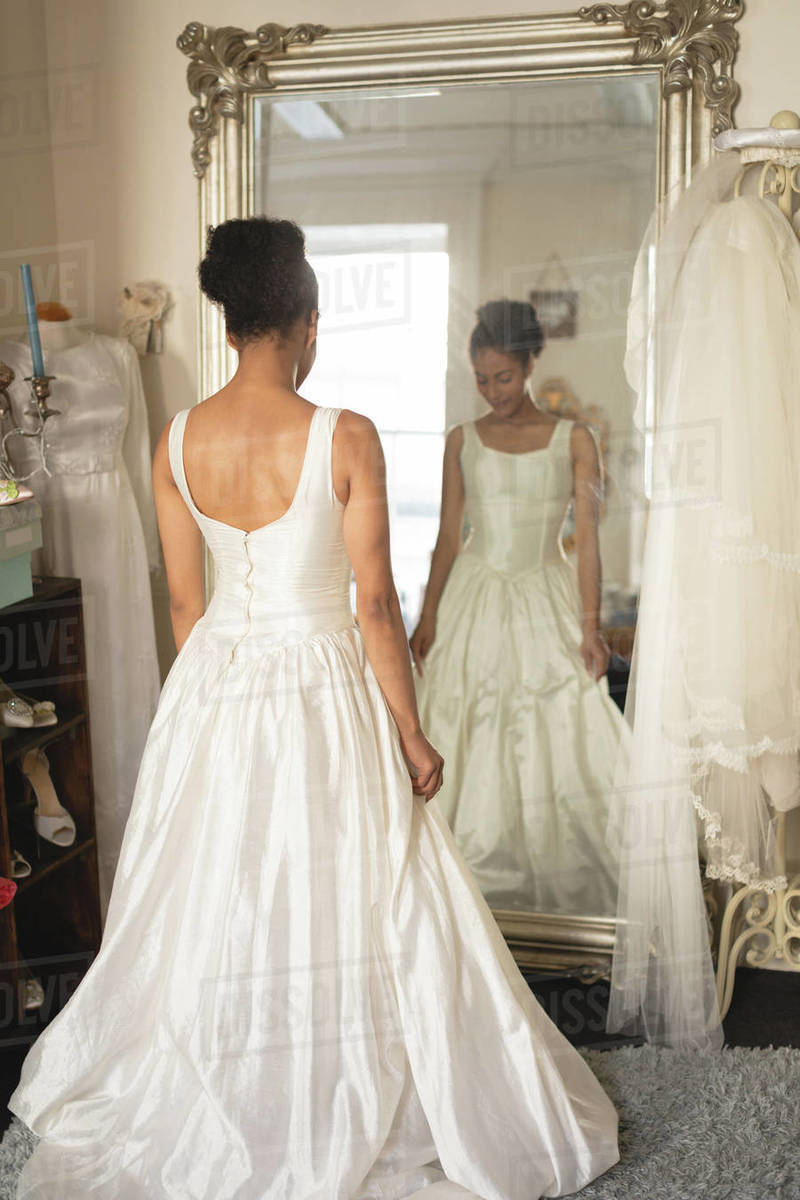 Young bride in a wedding dress looking into mirror at boutique ...