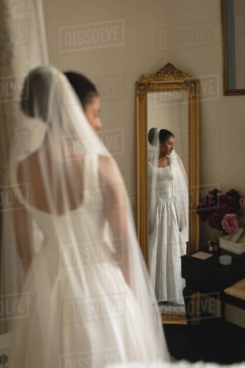 Reflection of young bride in a wedding dress in the mirror at ...