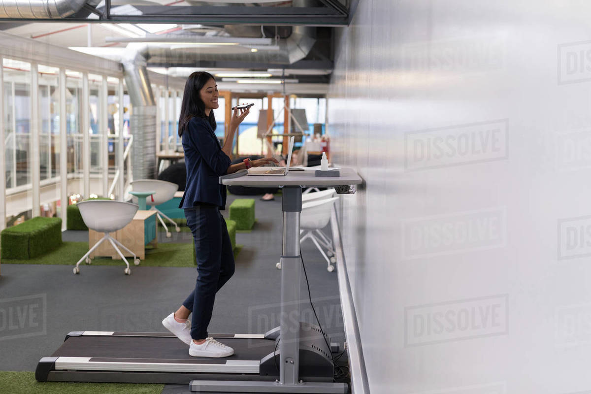 Female Executive Talking On Mobile Phone While Exercising On Treadmill In  Office