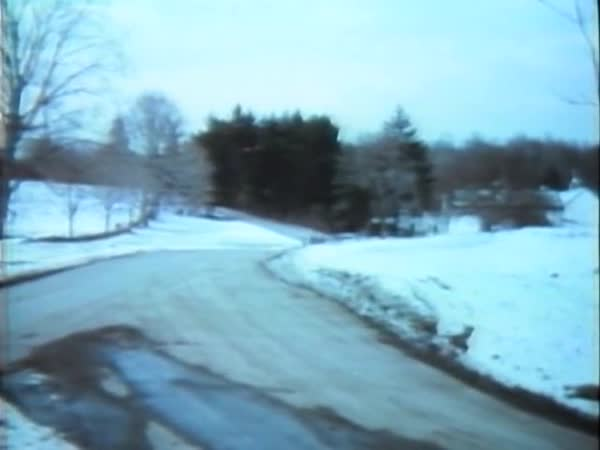 Handheld shot of car driving on road by snowy field Royalty-free stock video