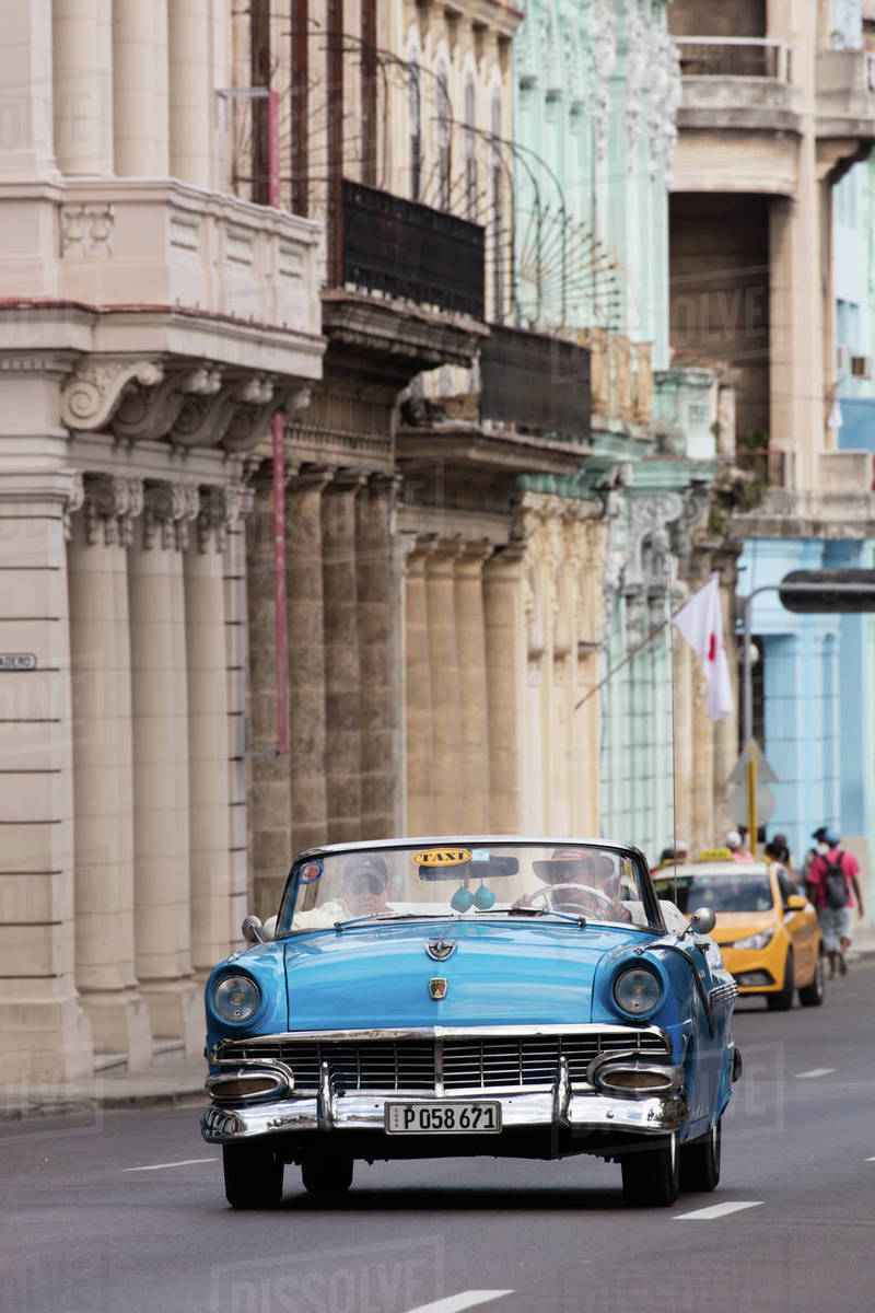 Blue convertible vintage taxi driving along Paseo de Marti in Havana, Cuba, West Indies, Caribbean, Central America Royalty-free stock photo