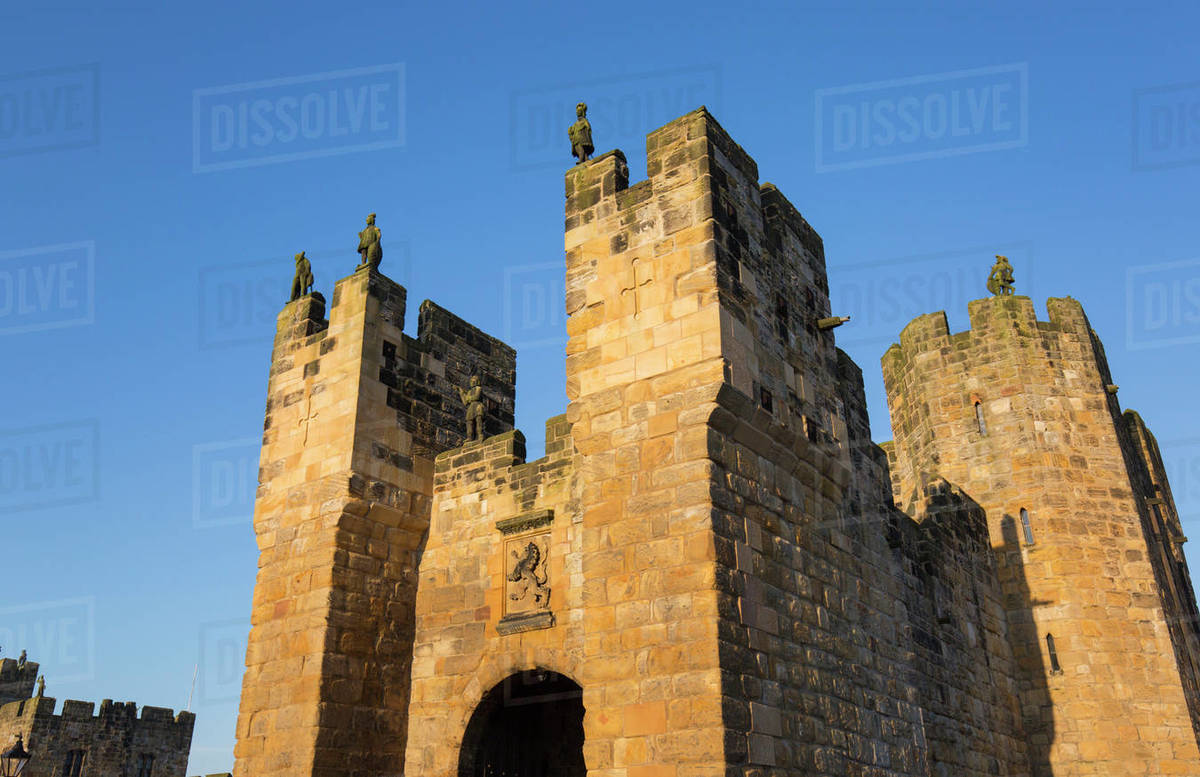 The medieval barbican and gatehouse of Alnwick Castle, sunset, Alnwick, Northumberland, England, United Kingdom, Europe Rights-managed stock photo