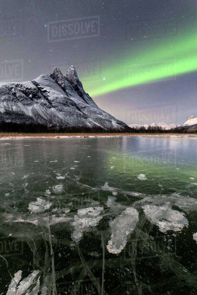 Ice bubbles of frozen sea and the snowy peak of Otertinden under the Northern Lights (aurora borealis), Oteren, Lyngen Alps, Troms, Norway, Scandinavia, Europe Royalty-free stock photo