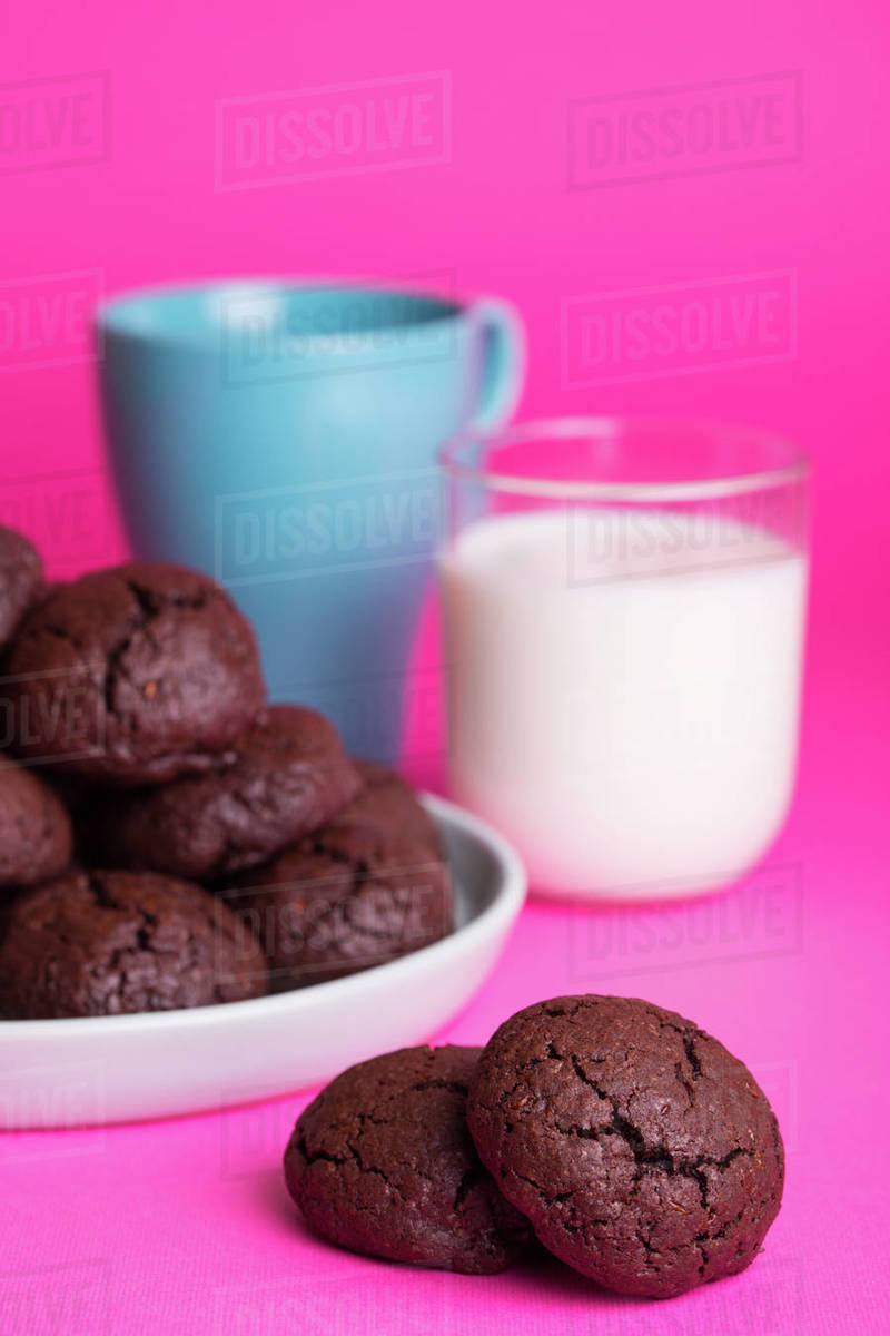 Homemade cakes - delicious and tasty chocolate chip cookies with a cup of milk on a bright background Royalty-free stock photo