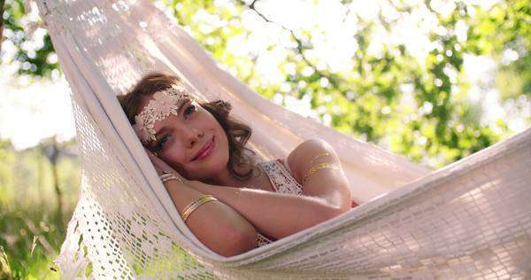 Girl in boho style clothing sleeping peacefully while lying in a hammock in a park on a sunny summer afternoon Royalty-free stock video