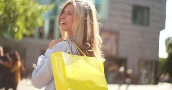 Portrait of a mature woman holding shopping bags over her shoulder and looking back at the camera while standing on a city street Royalty-free stock video