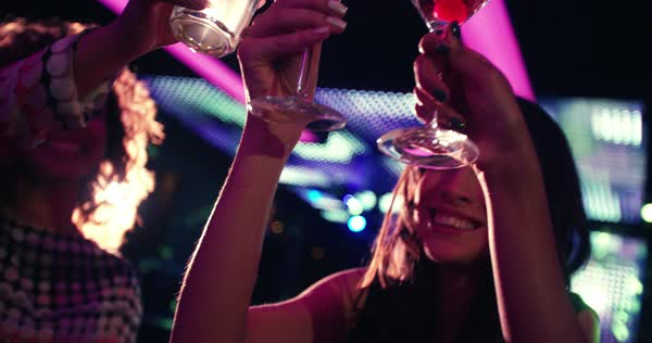 Attractive young joyful women happily toasting one another with martinis while sitting and smiling at the bar in a modern nightclub Royalty-free stock video