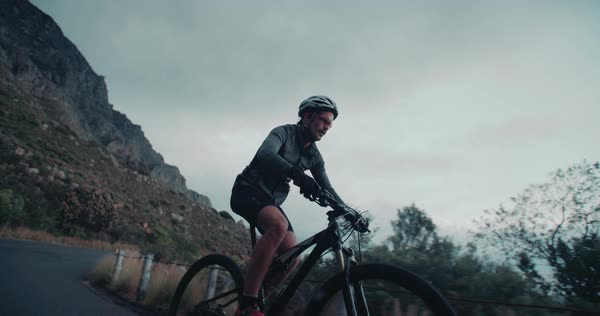 Silhouette side shot of cyclist riding on a mountain side road on an overcast day just after sunset in slow motion Royalty-free stock video