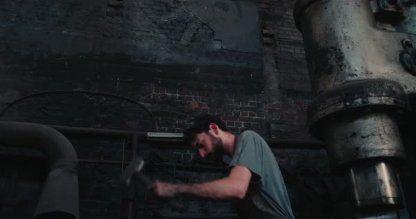 Environmental workplace portrait of a young adult craftsman hammering iron on an anvil in slow motion Royalty-free stock video