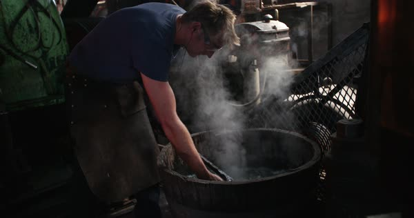 Adult craftsman standing in front of a barrel for cooling a glowing metal bar into water Royalty-free stock video