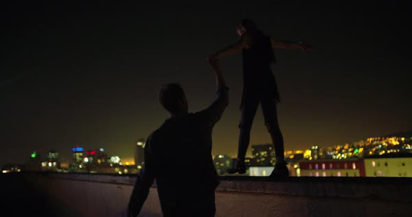 Man is holding hand with girlfriend who is balancing on rooftop edge with city lights in background at night Royalty-free stock video