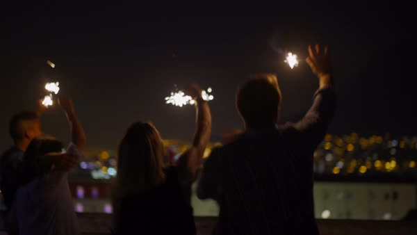 Young friends celebrating on the rooftop with sparklers at night with city lights in background at night Royalty-free stock video
