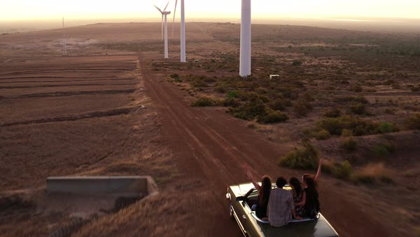 Group of friends dancing on the back seat of a convertible car while traveling in a wind farm Royalty-free stock video