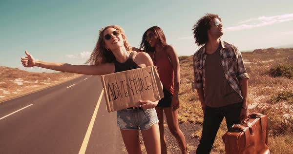 Hipster friends in the daytime stand on side of two lane highway hitchhiking while holding cardboard sign with the word Adventure written on it and sticking out thumb Royalty-free stock video
