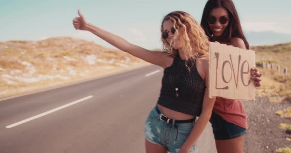 Hipster woman and hipster woman in the daytime stand on side of two lane highway hitchhiking while holding cardboard sign with the word Love written on it and sticking out thumb Royalty-free stock video