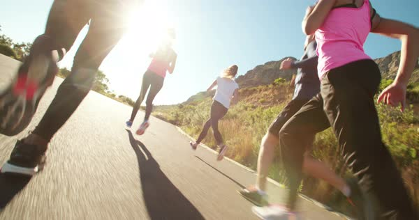 Low angle view of a young adult athletic woman running outdoors with her friends on sunset Royalty-free stock video